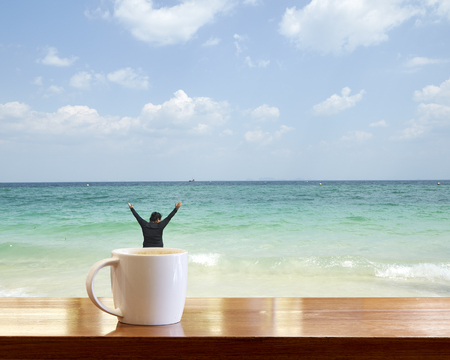 A cup of tasty coffee in a cafe on the beach. A delicious drink. Relax with a sea view. A woman in a happy mood 写真素材