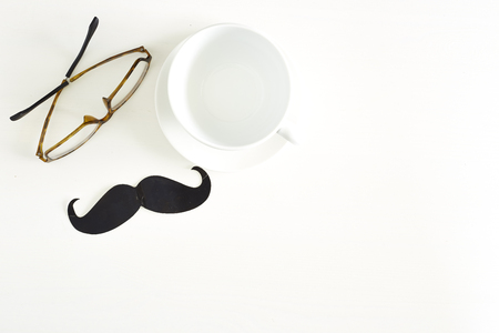 Happy Fathers Day inscription with mug and Spectacles on White wooden background. Greetings and presents