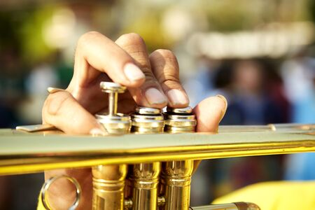 Brass vintage trumpet in gentle illumination. Jazzman holds the musical instrument in his hands while pushing on buttons.
