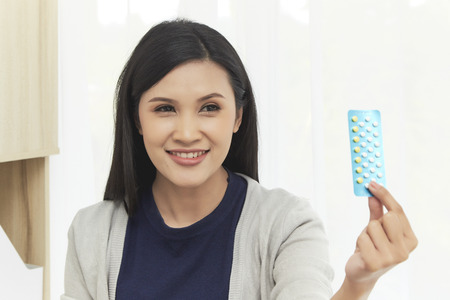 Happy young asian woman with pills at home, closeup. Want children, Gynecology concept Stock Photo