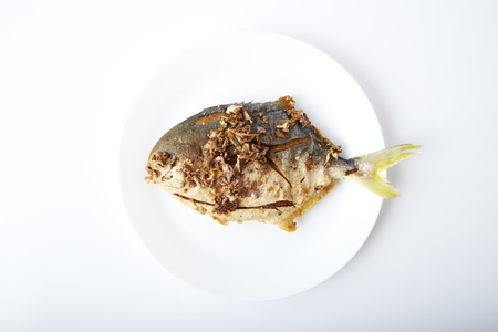 Fresh pomfret deep fried in dish isolated in white background clipping path