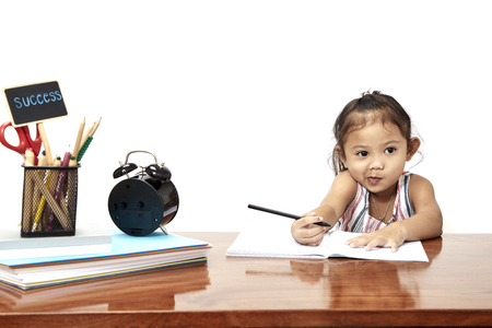 Asian little girl writing doing homework early childhood education, back go to school  版權商用圖片