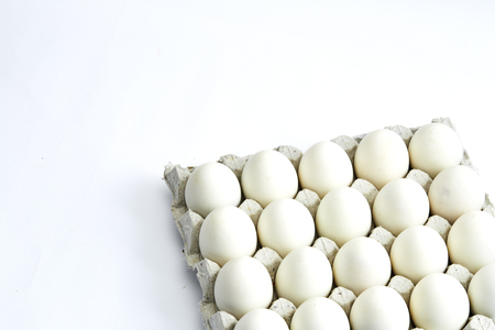 White eggs of a hen in harmless, cardboard packing on a white background. Stock Photo