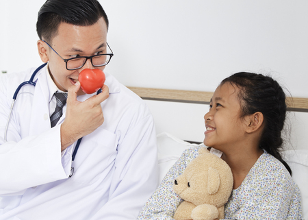 Care, Asian doctor with stethoscope holding red heart  and kid girl in the patient room, medical and health concept Stock Photo