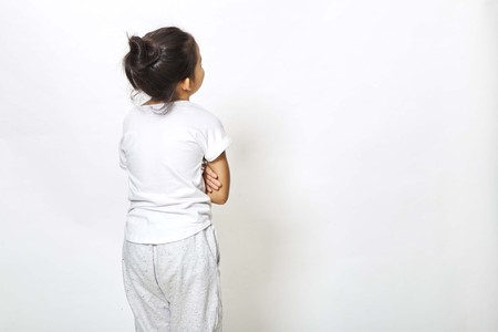 Back view of little girl looking at wall. Rear view on white background, Back to school concept Stock Photo