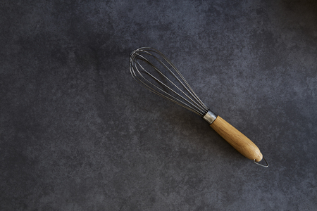 Kitchen Wire Whisk Eggs Beater on the wood table