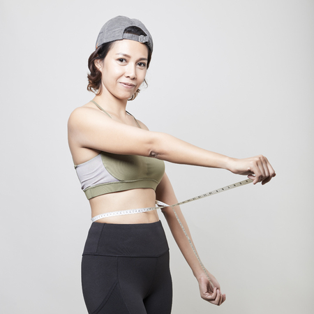 Fitness asian woman with measure tape on gray background 版權商用圖片