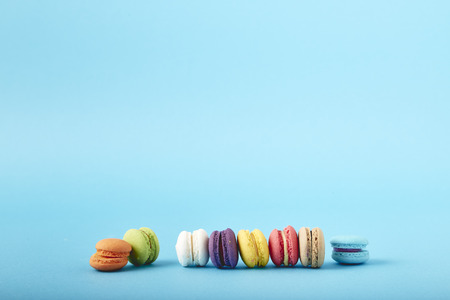 Sweet colorful French macaroon or macaron biscuits on blue background Stock Photo