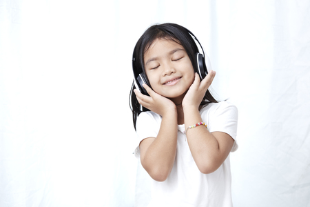 Cute little girl with smartphone and headphones listening to music and dancing Stock Photo