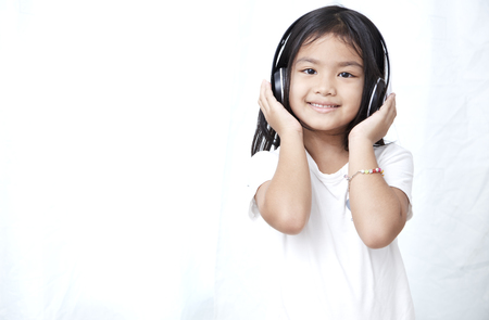 Cute little girl with smartphone and headphones listening to music and dancing Banco de Imagens