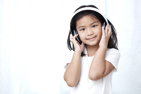 Cute little girl with smartphone and headphones listening to music and dancing 스톡 콘텐츠