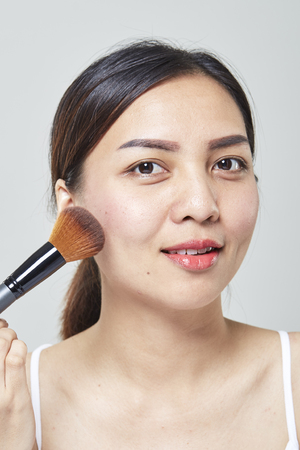Asian woman face portrait beauty skin care and applying cosmetic powder brush on white background. Natural makeup, skincare, cosmetology and plastic surgery concept.