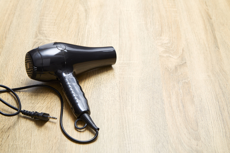 Modern hair dryer on wooden table background.