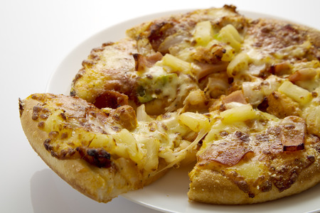 Whole Hawaiian pizza with pineapple and ham no white background