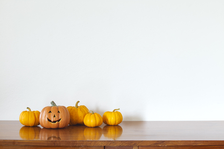 Orange halloween pumpkin on wooden table White wall background. Banque d'images