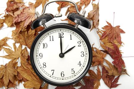 Bild des Herbst-Zeitwechsels, Fallback-Konzept, trockene Blätter und schwarze Vintage-Weckeruhr auf Holztisch im Freien am Nachmittag, für Text