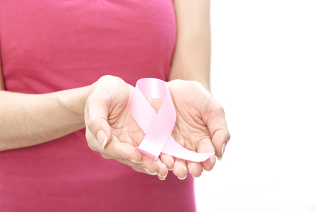 Smiling woman with breast cancer awareness ribbon on white background