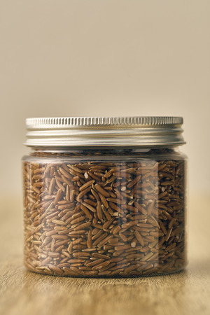 Red rice in glass Jar on wooden background, Natural light Stock Photo