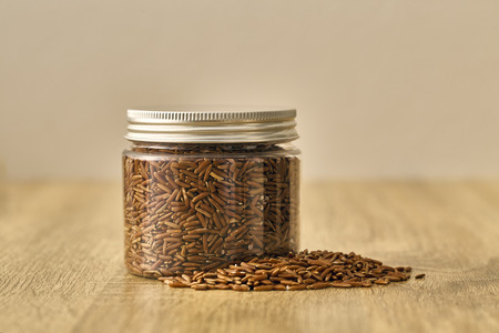 Red rice in glass Jar on wooden background Stock Photo