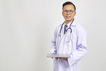 Smiling Asians doctor holding a digital tablet isolate on white