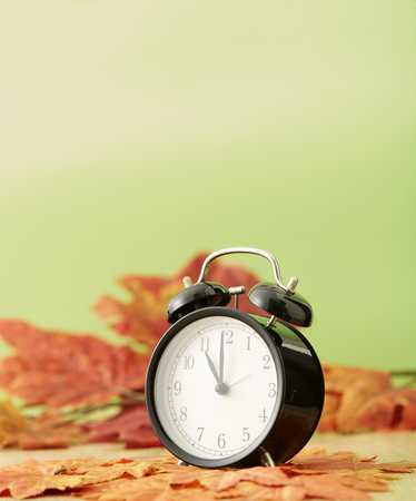 Black vintage clock with dried maple leaves on green background Stock Photo