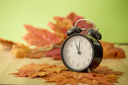 Black vintage clock with dried maple leaves on green background Archivio Fotografico