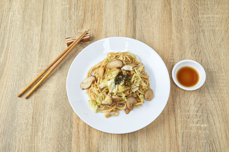 stir-fried yakisoba noodle with pork on wooden table  Asian food style, copy space and text. Фото со стока