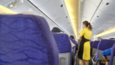 blurred Interior of commercial airplane with flight attandant serving passengers on seats during flight. Stewardess in dark Yellow uniform walking the aisle. Horizontal composition.