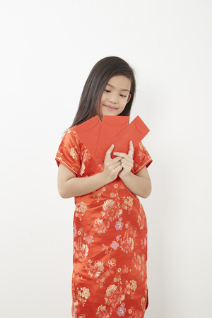 Chinese Girl eight year old girl with Chinese New Year 2019 With receive a red envelope inside of the banknote to bless those who have been happy on white backgrond, Concept New Year Sale, Chinese tradition Stock Photo