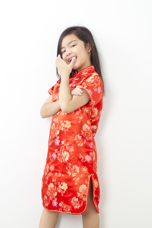 Girl child 8 years in chinese dress traditional cheongsam New year 2019 with gesture of congratulation on white wall background
