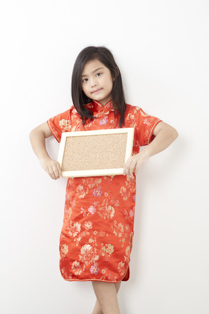 Girl child 8 years in chinese dress traditional cheongsam New year 2019 with holding a empty cork board Banco de Imagens