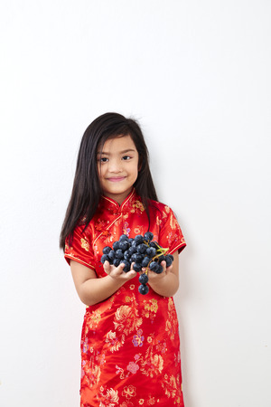 Girl child 8 years in traditional Chinese dress  New year 2019 with holding a Eating Grape bunch gestures on white wall background