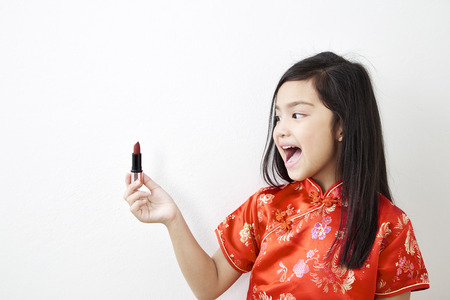 Little girl in Chinese dress With red lipstick on white wall background, Beauty and fashion concept