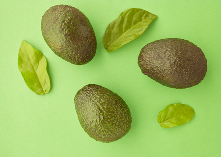 Avocado on pastel Green background minimal creative idea. space for a text, flat lay, view from above