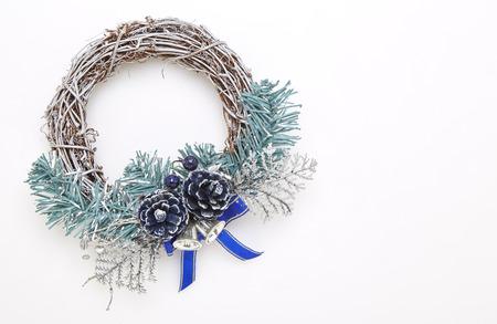Corona de Navidad verde y azul con adornos en la pared blanca Foto de archivo