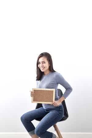 Beautiful young Asian woman Bulletin Board guts pose gesture sitting in a chair on white wall