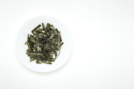 Seal of dried seaweed in a white plate on a white table. Light emulates natural light with space for design.