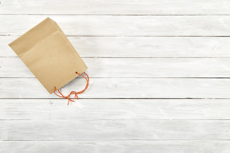 Shopping bag paper brown surprise gift on white wooden with copy space, Empty space for design, biodegradable material friendly to the environment.