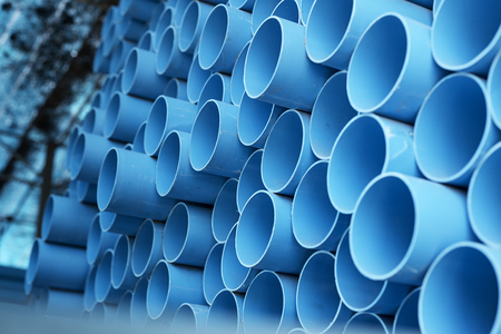 background of colorful  Blue PVC pipes stacked in construction site Stockfoto
