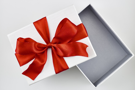 Opened white Christmas gift box with lid red bow and ribbon isolated on white