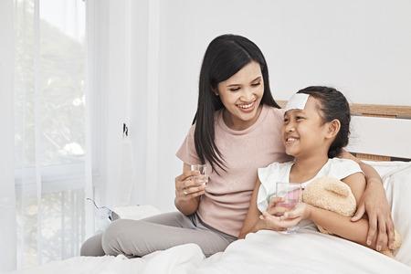 madre sta dando la medicina a sua figlia di prendere farmaci in camera da letto background.Concept di buona assistenza sanitaria per la famiglia.