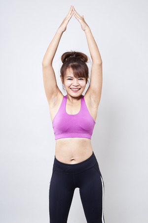 Aziatische vrouw die sportkleding draagt en haar lichaam op witte achtergrond toont Stockfoto