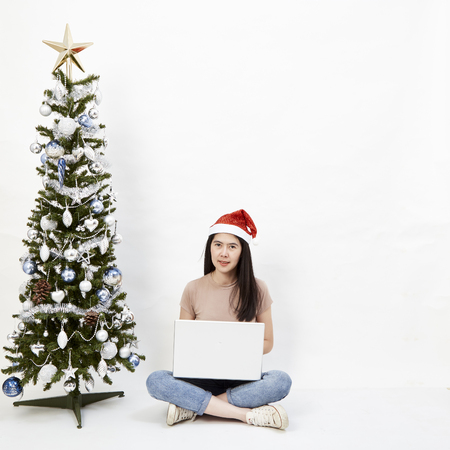 Christmas Asian girl happy with her success while working on a laptop on a white background