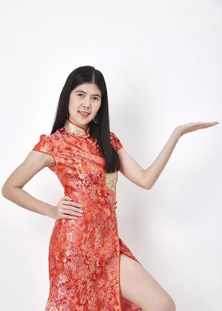 Portrait Beautiful Asian woman Chinese girl hands showing something, in traditional red cheongsam standing on white background, Empty space for design, Business concept