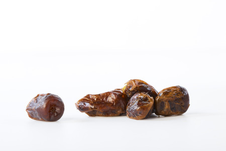 Dried dates (fruits of date palm Phoenix dactylifera) on a white background.