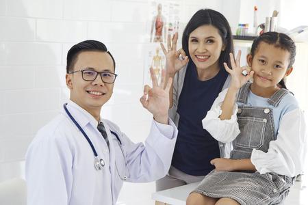 Arzt mit medizinischem Klinikhintergrund für Pflegefachkräfte und Patientenvertrauen in das Hospitality-Konzept des Krankenhauses, Mutter und asiatische Tochter kommen zum Arzt. Standard-Bild