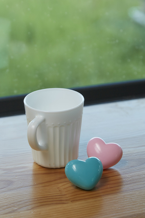 White coffee cup white Pink heart with blue and green background in morning sunlight Banco de Imagens