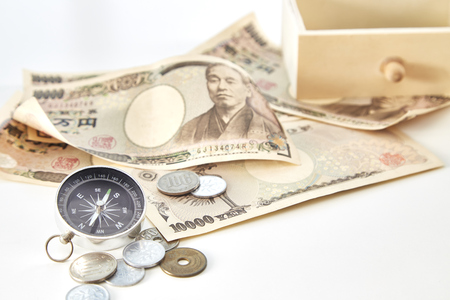Compass with Japanese yen banknotes and Japanese yen coin on white background