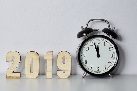Happy New Year concept with alarm clock and wooden number 2019 on White Wall background, Copy space. Stock Photo