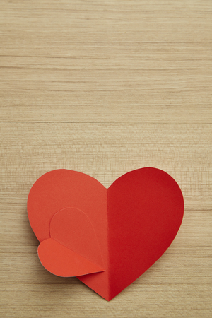 Valentine's day red paper heart on abstract wooden background with for text love and young happy joyful, paper cut red heart, love Invitation card